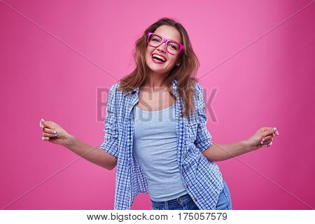 Close-up shot of funny casual girl dances in the studio beguiles girl having fun isolated over pink background. Female in casual outfit dancing and spending time with pleasure