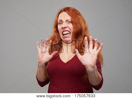 Close-up shot of redhead woman with freckles feeling aversion. Holding two hands in order to protect from something