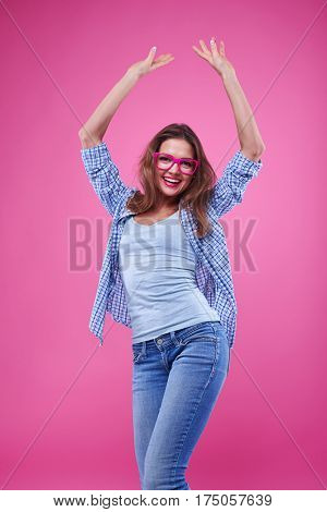 Mid shot of young girl having fun isolated over pink background. Female in casual outfit dancing and spending time with pleasure
