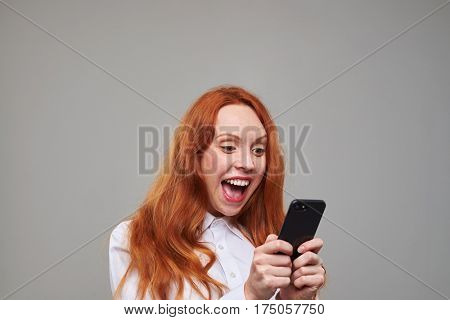 Close-up of joyful red hair girl using mobile phone isolated over background. Girl posing isolated over background in the studio
