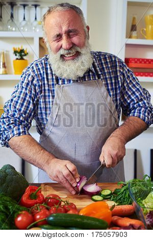 Close-up of mature man chopping an onion. Stinging eyes and tears when cutting onions to prepare dinner. Shedding tears and wiping with the back of her hand. Man crying while chopping an onion