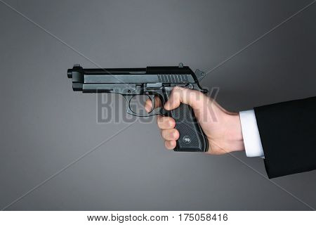 Man's hand holding gun on color background