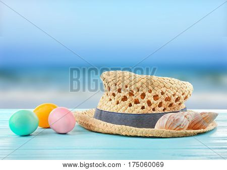Easter eggs with hat and seashells on wooden table at shore