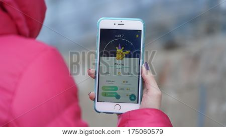 Samara, Russia - March 7, 2017: woman playing pokemon go on his iphone 6s Plus. pokemon go multiplayer game with elements of augmented reality. Pikachu was caught. Second generation of Pokemon