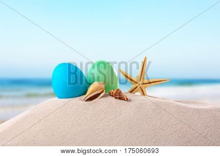 Easter eggs with seashells on sand at shore