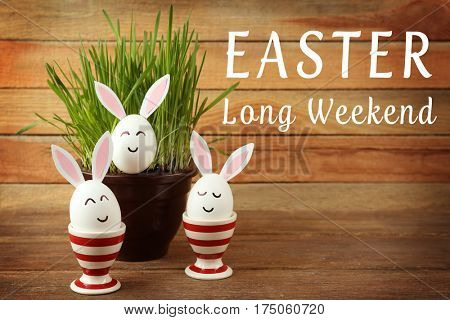 Text EASTER LONG WEEKEND and decorated eggs with plant on wooden background
