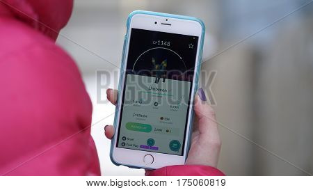 Samara, Russia - March 7, 2017: woman playing pokemon go on his iphone 6s Plus. pokemon go multiplayer game with elements of augmented reality. Umbreon was caught. Second generation of Pokemon