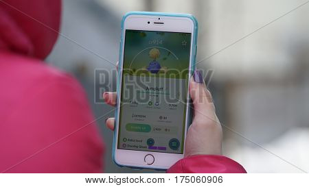 Samara, Russia - March 7, 2017: woman playing pokemon go on his iphone 6s Plus. pokemon go multiplayer game with elements of augmented reality. Jumpluff was caught. Second generation of Pokemon