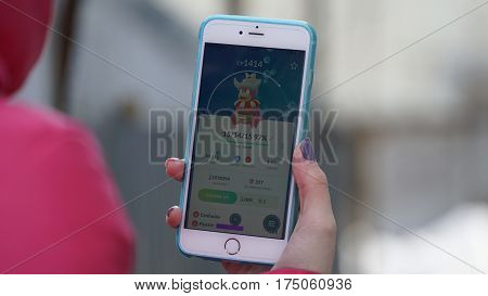 Samara, Russia - March 7, 2017: woman playing pokemon go on his iphone 6s Plus. pokemon go multiplayer game with elements of augmented reality. Slowking was caught. Second generation of Pokemon