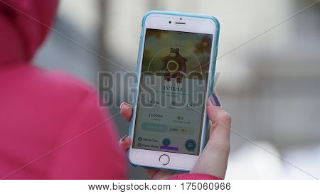 Samara, Russia - March 7, 2017: woman playing pokemon go on his iphone 6s Plus. pokemon go multiplayer game with elements of augmented reality. Ursaring was caught. Second generation of Pokemon