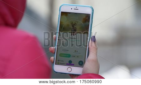 Samara, Russia - March 7, 2017: woman playing pokemon go on his iphone 6s Plus. pokemon go multiplayer game with elements of augmented reality. Stantler was caught. Second generation of Pokemon