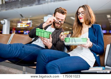 Elegant business couple eating with lunch boxes sitting at the waiting hall in the airport. Having a snack during business trip