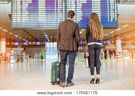Business couple looking at the timetable standing at the airport. Business travel concept