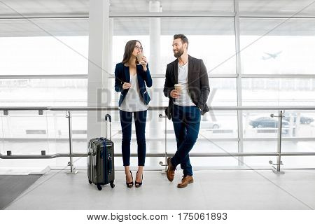 Business couple standing together with baggage and coffee cups near the window at the departure area at the airport