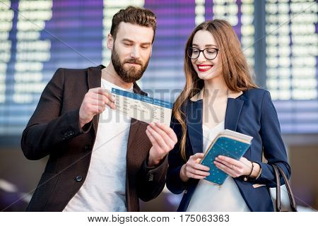 Business couple looking at the boarding pass checking the departure time in front of the airplane schedule at the airport