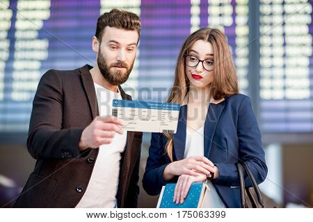 Stressed business couple looking at the boarding pass checking the departure time in front of the airplane schedule at the airport