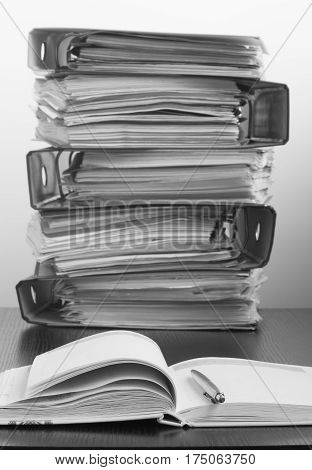 Seven Five folders with documents stacked in a pile on the table. Black and white photo