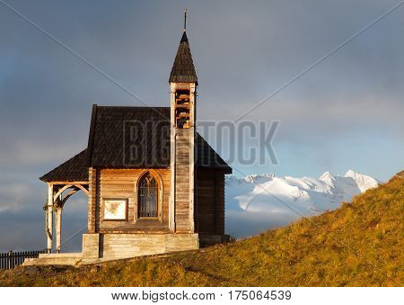 Morning view of small wooden church or chapel on the mountain top Col di Lana and Mount Marmolada Alps Dolomites mountains Italy