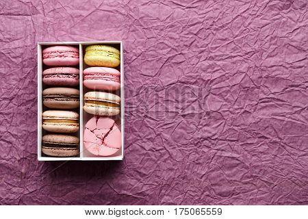 Box of colorful macarons on creased paper textured background, space for texting