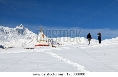 View of white buddhist stupa near ice lake (Kicho Tal) and Annapurna range with two tourists mount Gangapurna or Ganggapurna round Annapurna circuit trekking trail Annapurna area Nepal