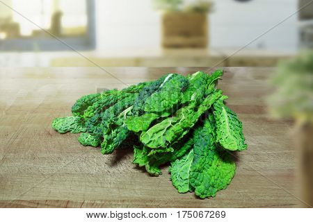 Some loose kale leaves on a wooden table in a rustic kitchen. Empty copy space for Editor's content.