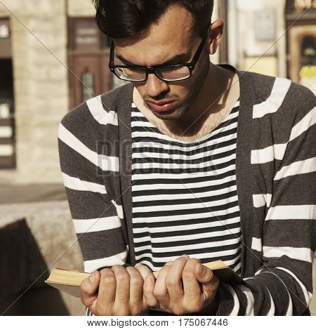 young man with coffee reading book in old center of europe city Lviv