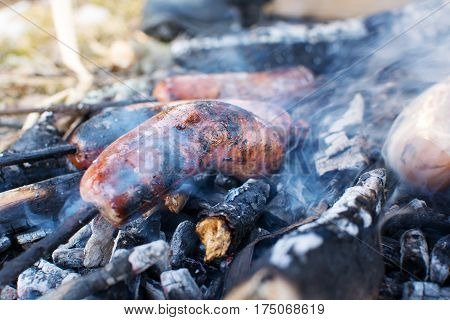Sausages Roasting On Burning Embers Outdoors