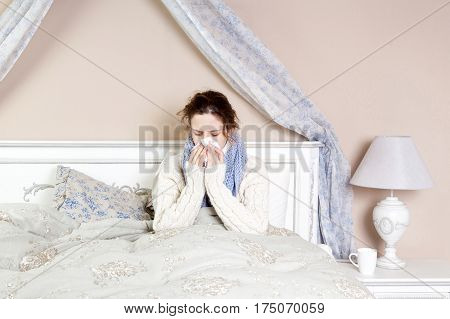 Sick woman with terrible sore throat. Closeup image of young woman with red nose in bed with thick scarf and touching her neck and head feeling pain