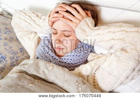 Flu or cold. Closeup top view image of frustrated young woman with blue scarf and suffering from terrible headache while lying in bed.