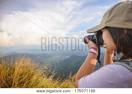 Side face of hiker teens girl wear caps with digital camera taking photo beautiful landscape natural of sierra and sky on mountain at viewpoint Phu Chi Fa Forest Park Chiang Rai Thailand