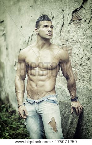 Muscular young latino man shirtless in jeans in front of concrete wall, showing sexy body with ripped abs, pecs and arms