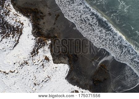 Aerial image of a snowy beach with incoming wave
