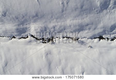 Aerial image of a small mountain creek after heavy snowfall