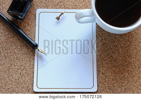 Bulletin board desk top with coffee, pen and ink, blank note with arrow thumbtack.