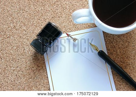 Bulletin board desktop with coffee, pen and ink, and blank note paper with arrow thumbtack.