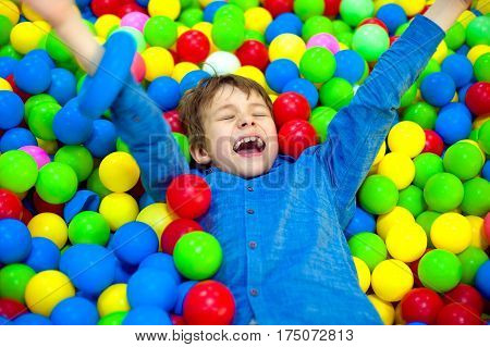 Happy boy playing in colorful balls. Happy child playing at colorful plastic balls playground high view