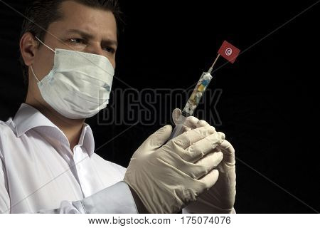 Young Man As A Doctor Gives A Medical Injection To Tunisian Flag On A Black Background