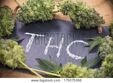 Medical marijuana background with cannabis leaves and buds sorrounding the word THC hand written on dark board