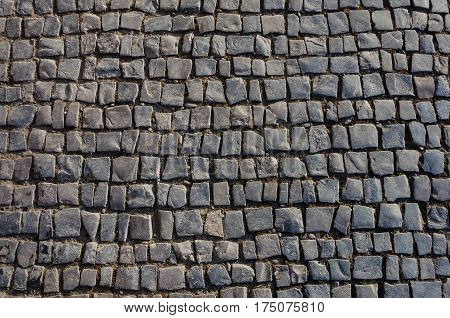 Fragment of old gray cobblestone pavement texture