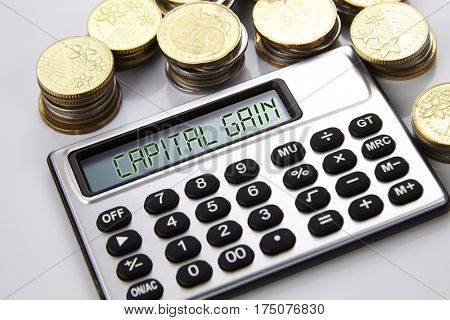 few stacks of coins and calculator with text on screen capital gain