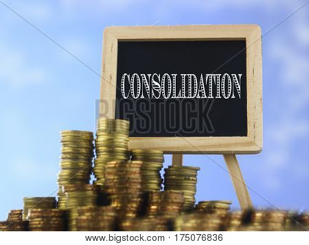 Many piles of coins against  blue sky and mini blackboard with text consolidation