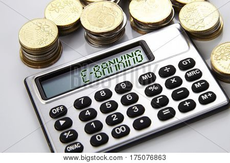 few stacks of coins and calculator with text on screen e-banking