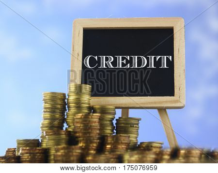 Many piles of coins against  blue sky and mini blackboard with text credit