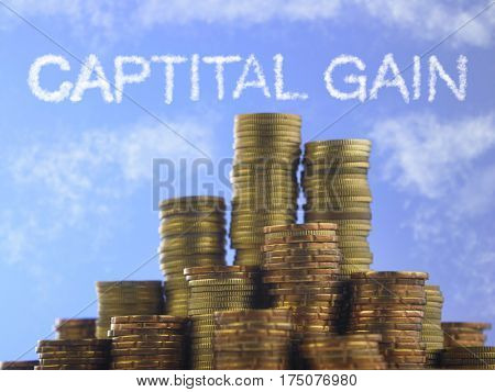 Many piles of coins against  blue sky with text capital gain