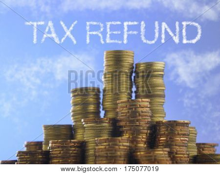 Many piles of coins against  blue sky with text tax refund