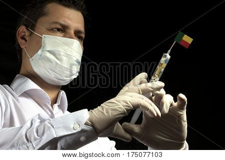 Young Man As A Doctor Gives A Medical Injection To Benin Flag On A Black Background