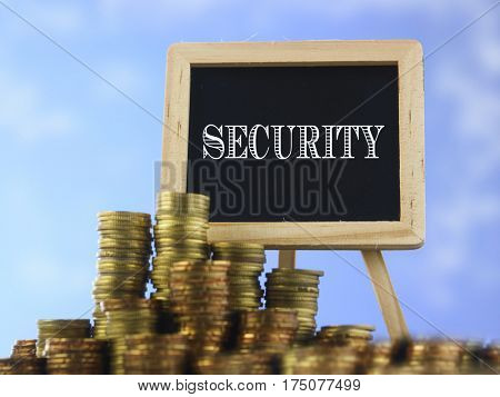 Many piles of coins against  blue sky and mini blackboard with text security