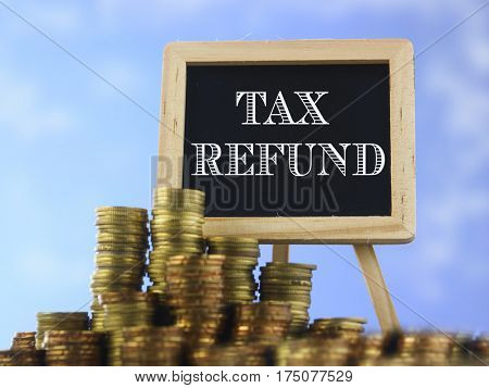 Many piles of coins against  blue sky and mini blackboard with text tax refund