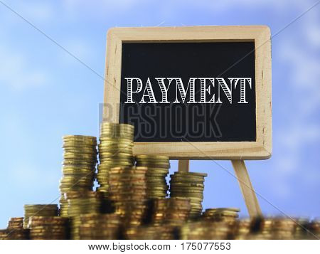 Many piles of coins against  blue sky and mini blackboard with text payment