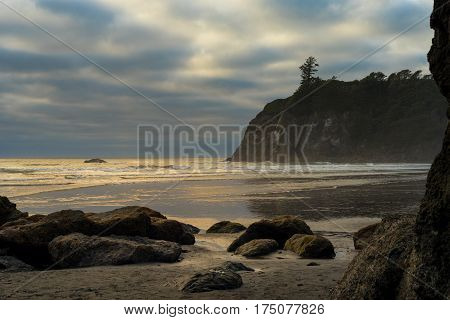 Golden waves from late afternoon sun break on Washington's Ruby Beach under clouds and mist